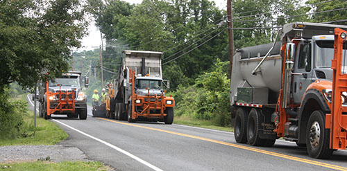 Photo: Trucks applying hot mix asphalt (HMA) resurfacing