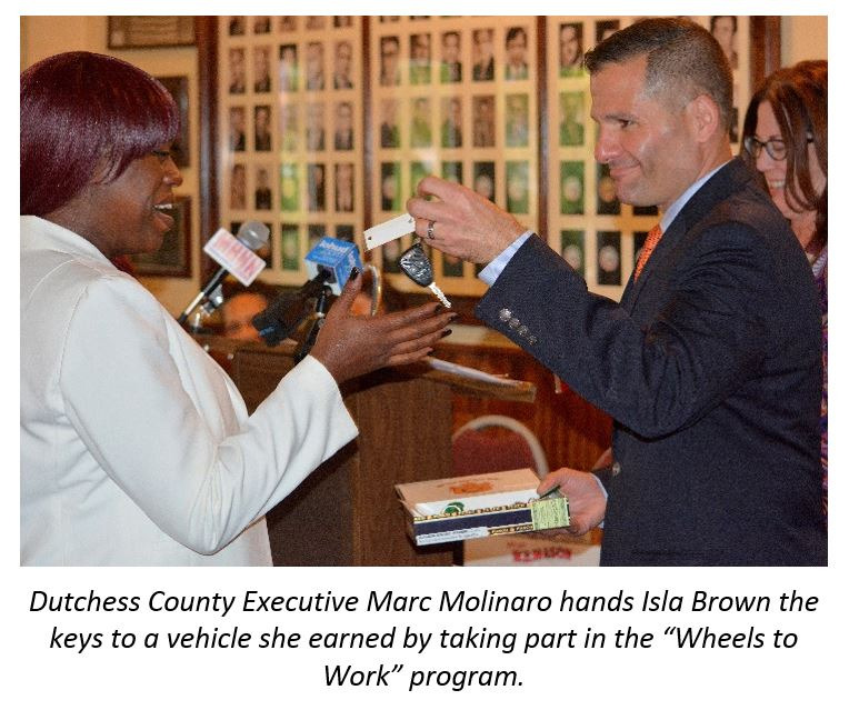 "Dutchess County Executive Marc Molinaro hands Isla Brown the keys to a vehicle she earned by taking part in the ""Wheels to Work"" program"