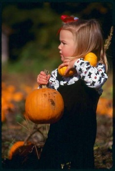 Child carrying pumpkins image