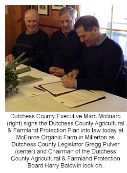 Dutchess County Executive Marc Molinaro (right) signs the Dutchess County Agricultural & Farmland Protection Plan into law today at McEnroe Organic Farm in Millerton as Dutchess County Legislator Gregg Pulver (center) and Chairman of the Dutchess County Agricultural & Farmland Protection Board Harry Baldwin look on.