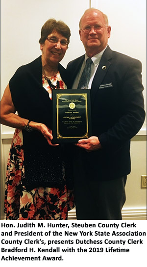 Hon. Judith M. Hunter, Steuben County Clerk and President of the New York State Association of County Clerk's, presents Dutchess County Clerk Bradford H. Kendall with the 2019 Lifetime Achievement Award.