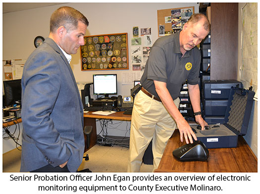 County Executive Molinaro with Probatin Officer demonstrating electronic monitoring equipment